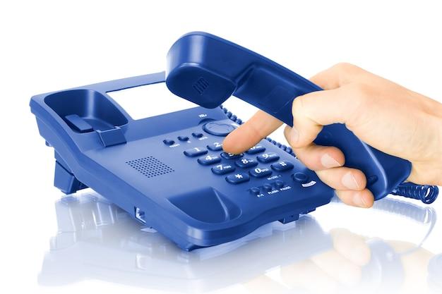 Téléphone de bureau bleu avec main isolé sur blanc