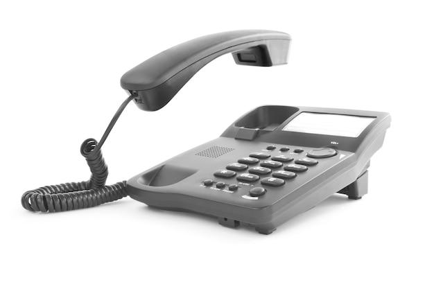 Téléphone de bureau noir avec le combiné soulevé vers le haut isolé sur blanc