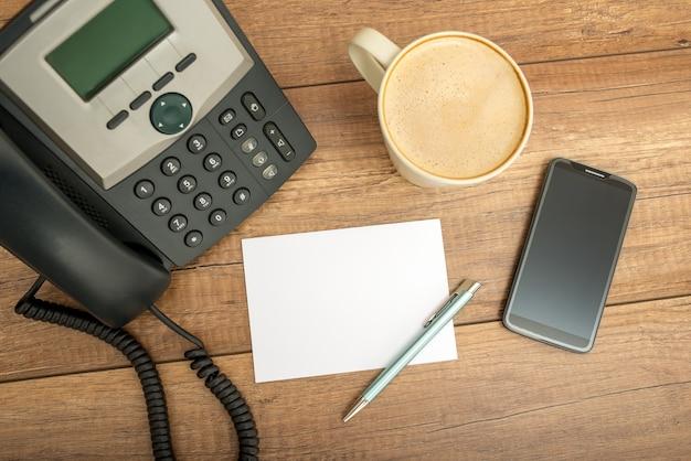 Téléphone de bureau noir filaire, papier à lettres vierge, stylo, une tasse de cappuccino et un téléphone intelligent, sur une table en bois, prise de vue en grand angle.