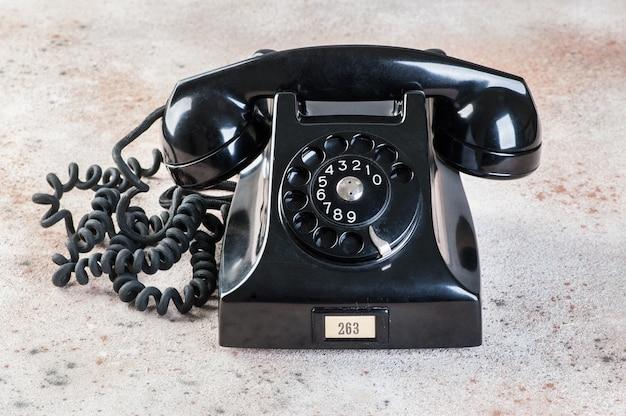 Téléphone à cadran noir antique sur fond de béton.