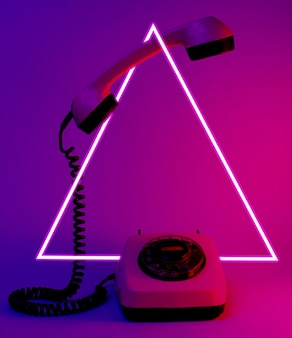 Téléphone à cadran de style ancien avec poignée de téléphone en flèche, néon bleu rouge, années 80
