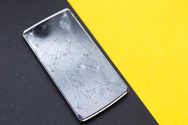 Un téléphone cassé sur fond jaune et noir. appareil écrasé avec écran cassé représentant un accident. écran texturé avec dommages. verre foncé d'un écran.