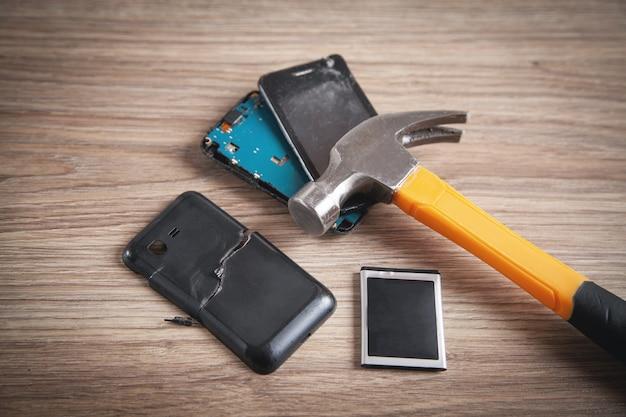 Téléphone cassé et marteau sur le fond en bois.