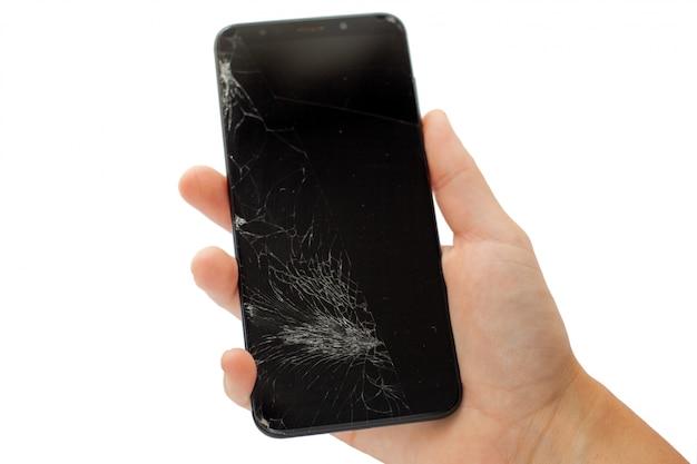 Téléphone cassé noir à la main sur l'écran tactile fissuré blanc