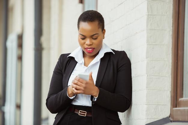 Téléphone défilant femme d'affaires afro-américaine en tenue de bureau souriante a l'air confiante
