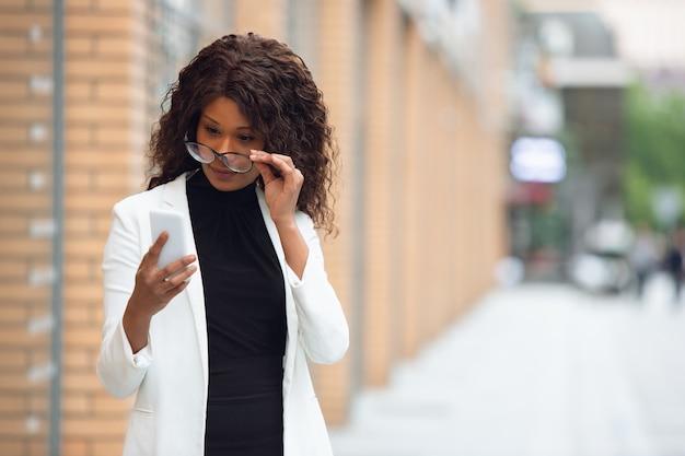 Téléphone à défilement bavarder femme d'affaires afro-américaine en tenue de bureau souriant