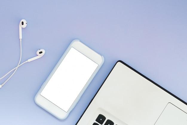 Un téléphone avec un écran blanc, un ordinateur portable et des écouteurs sur fond bleu. gadgets flat lay et place pour le texte.