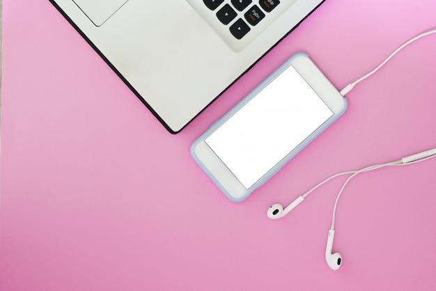 Un téléphone avec un écran blanc, un ordinateur portable et des écouteurs sur fond rose et avec une place pour le texte.