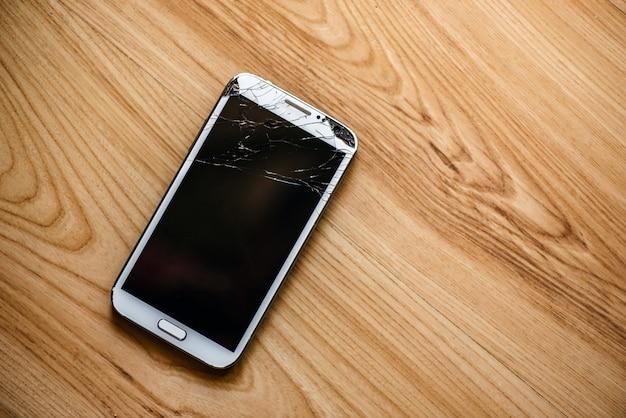 Téléphone avec un écran cassé sur un fond en bois.