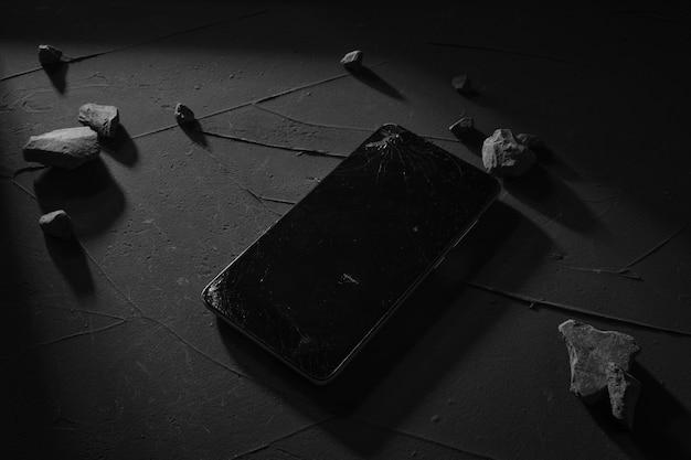 Téléphone à écran cassé sur une table en béton avec une lumière dure, des ombres