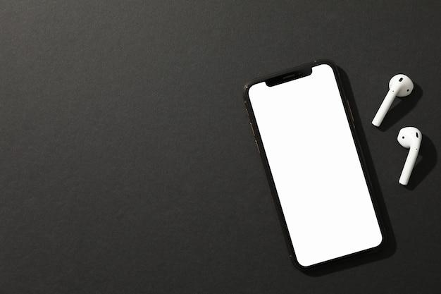 Téléphone avec écran vide et casque sur fond noir, vue de dessus