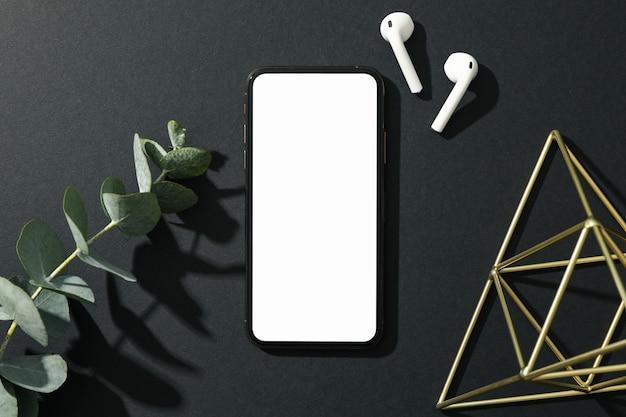 Téléphone avec écran vide sur fond décoré noir, vue de dessus