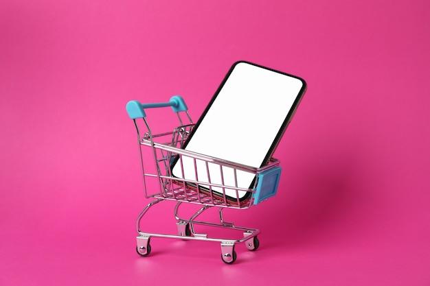 Téléphone avec écran vide et panier sur la surface rose