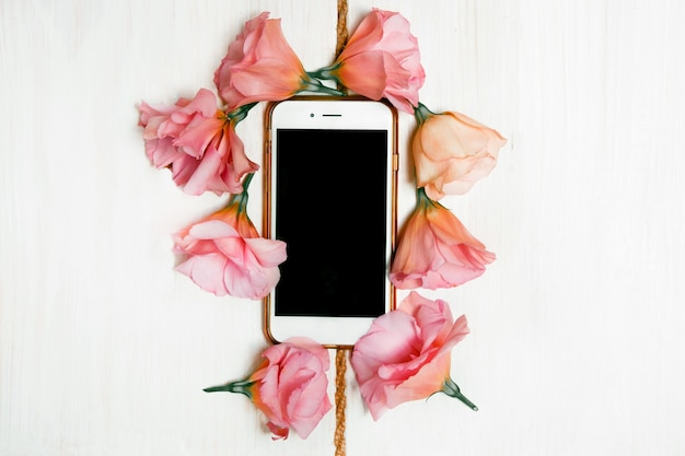 Le téléphone est encadré d'eustomas rose pâle.