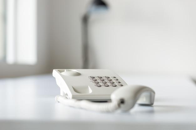 Téléphone fixe blanc avec combiné hors ligne sur un bureau blanc.
