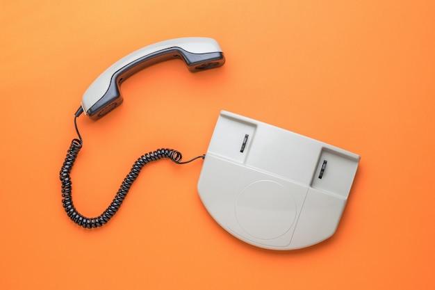 Un téléphone gris avec le récepteur éteint sur un fond orange. mise à plat.