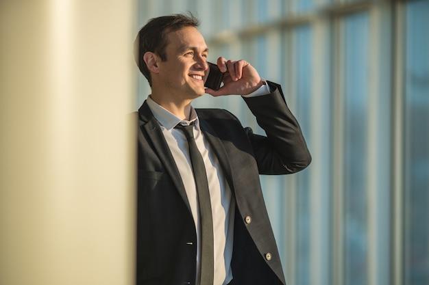 Le téléphone d'homme d'affaires près de la colonne
