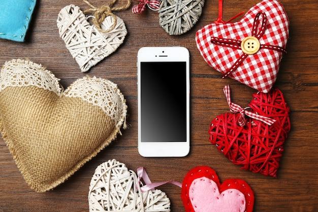 Téléphone intelligent blanc avec des coeurs sur un bureau en bois.