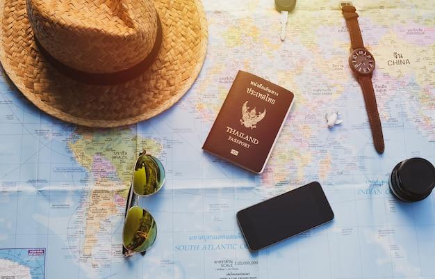 Téléphone intelligent, clé, objectif, avion, chapeau de paille et passeport sur carte avec effet de lumière solaire