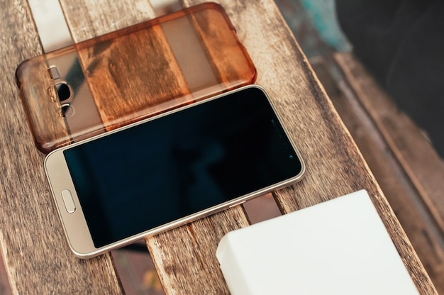 Téléphone intelligent et couvercle sur table en bois, à vendre