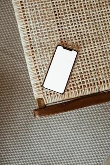 Téléphone intelligent à écran blanc sur chaise en rotin. mise à plat, vue de dessus