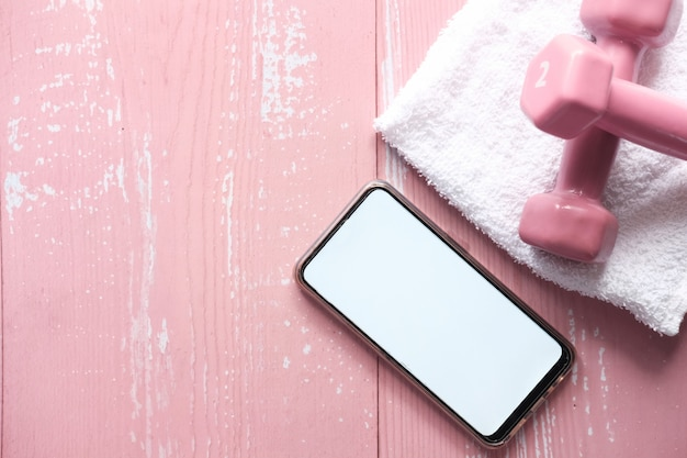 Téléphone intelligent avec équipement sportif sur espace rose.