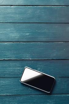 Téléphone intelligent sur fond de table en bois