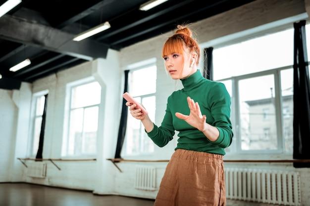 Téléphone intelligent. instructeur de yoga professionnel aux cheveux roux portant un col roulé vert tenant un téléphone à la main