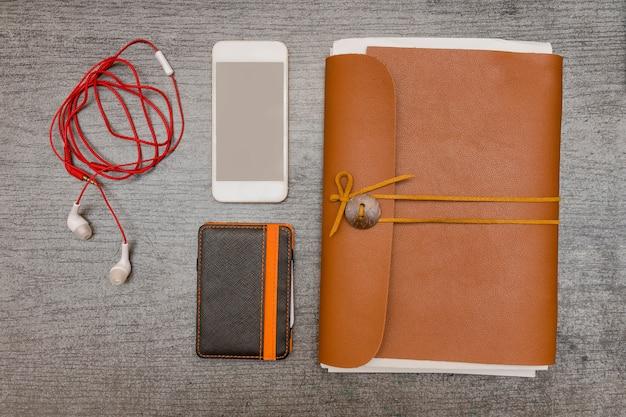 Téléphone Intelligent, Portefeuille, écouteurs Et Un Ordinateur Portable En Cuir Sur Une Table Noire. Vue De Dessus Photo Premium