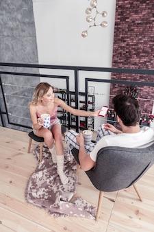 Téléphone intelligent. slim blonde femme aux cheveux longs portant des chaussettes blanches épaisses tenant un smartphone dans sa main tout en montrant une photo à son mari