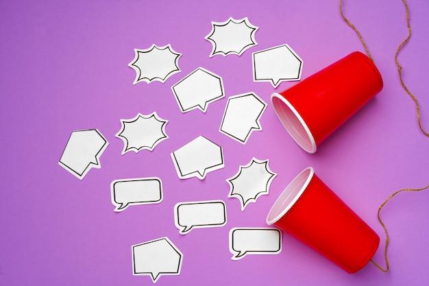 Téléphone jouet fait de gobelets en plastique et ficelle avec bulles sur surface violette
