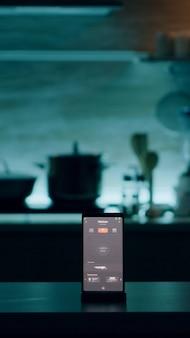 Téléphone avec logiciel intelligent placé sur une table dans la cuisine sans personne à l'intérieur, contrôlant la lumière avec une application de haute technologie