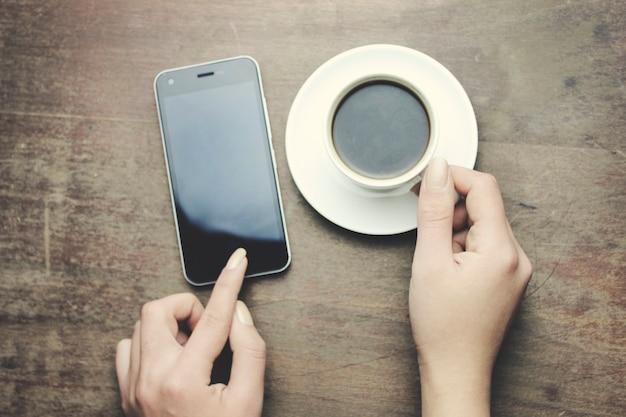 Téléphone de main de femme et café sur la table en bois