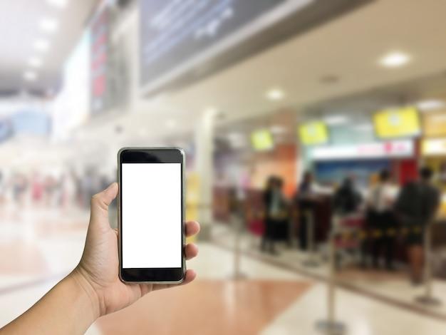 Téléphone de maintien de la main avec vérification dans l'arrière-plan de l'aéroport