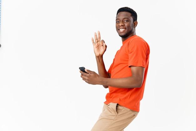 Téléphone mobile africain d'homme émotif faisant des gestes avec ses mains et t-shirt orange