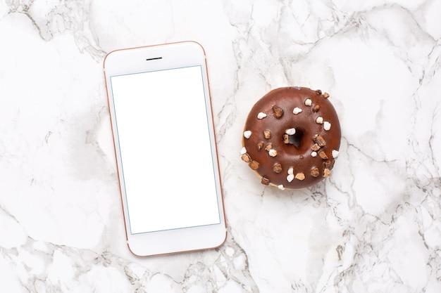 Téléphone mobile et beignet sucré sur fond de marbre