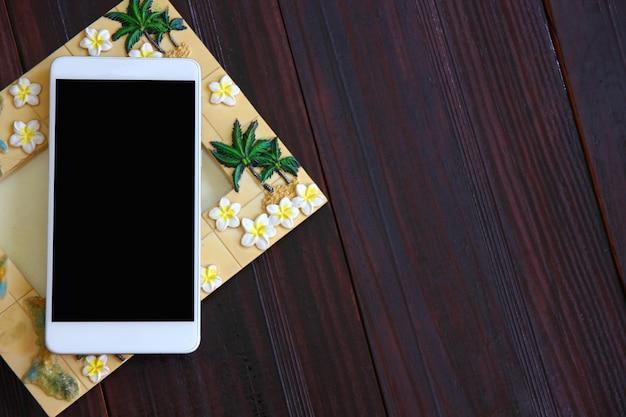 Téléphone mobile blanc vierge avec cadre photo sur plancher en bois brun