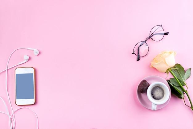 Téléphone mobile, café chaud avec une fleur rose de femme lifestyle sur fond rose