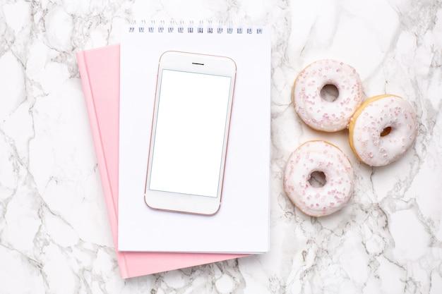 Téléphone mobile, cahier rose et beignet sucré sur fond de marbre