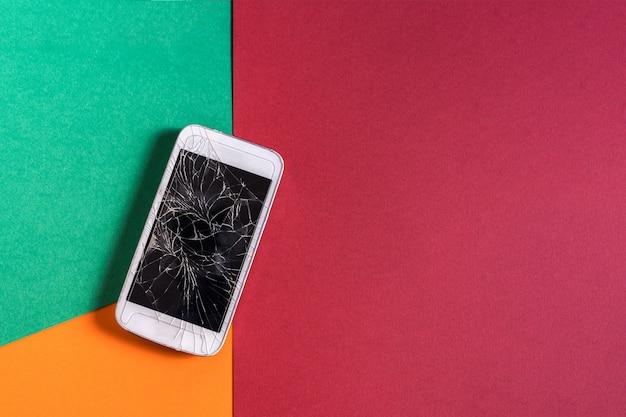 Téléphone mobile cassé avec écran fissuré sur une table colorée, mise à plat.