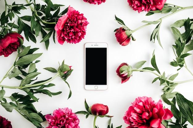 Téléphone mobile dans le cadre de fleurs de pivoines roses sur une surface blanche