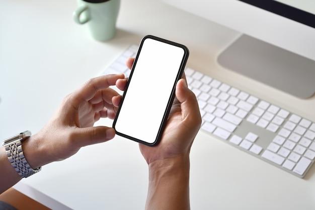 Téléphone mobile à écran blanc dans la main du mâle sur l'espace de travail studio avec fournitures de bureau.