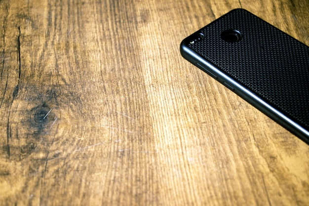 Téléphone mobile à écran blanc sur un fond de planche de bois marron avec espace de copie