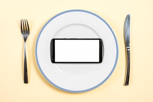 Téléphone mobile avec écran blanc sur plaque avec fourchette et couteau à beurre sur fond beige