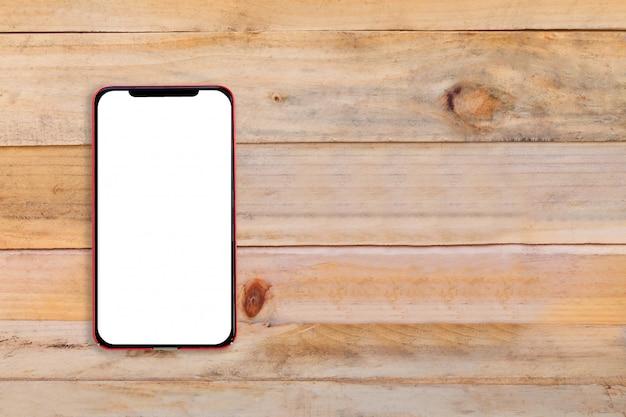 Téléphone mobile à écran blanc sur une table en bois.