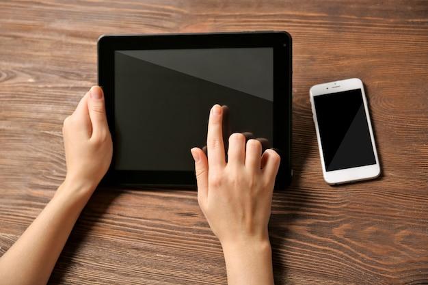 Téléphone mobile et mains féminines à l'aide de tablette, sur le fond en bois