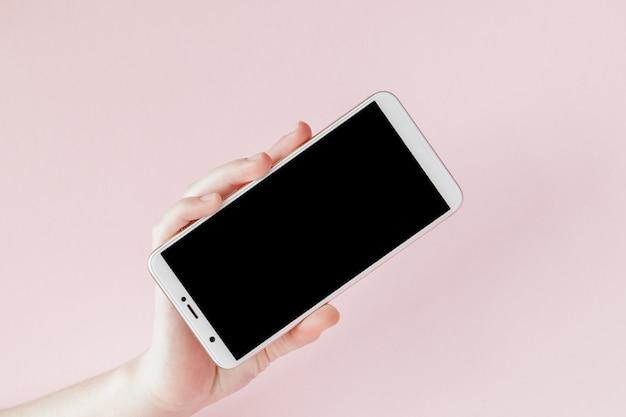 Téléphone mobile moderne dans une main de femme sur fond rose