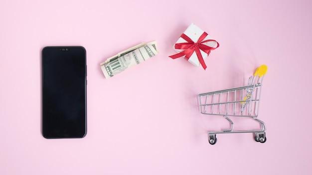 Téléphone mobile avec un panier miniature et de l'argent sur une surface rose.