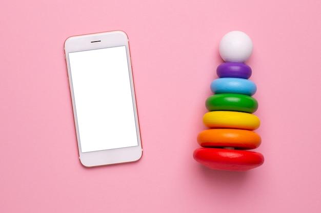 Téléphone mobile et pyramide en bois pour enfants colorés sur une vue de dessus de fond rose