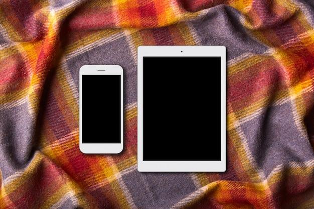 Téléphone mobile et tablette sur une couverture colorée chaude